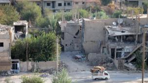 A pick-up truck drives past damaged buildings in Syria's eastern town of Deir Ezzor, on 2 September 2013.