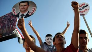 A protester holds a placard of Syrian President Bashar al-Assad during a rally in Hatay, Turkey, on 1 September 2013