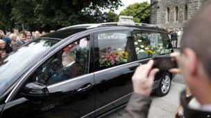 People watch the coffin of Irish poet Seamus Heaney leave the Church of the Sacred Heart in Donnybrook, Dublin, Ireland. Heaney will be buried in his native Bellaghy, in County Londonderry.
