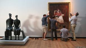 Workmen install a painting by Francis Bacon