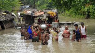 Flood-affected villagers carry their belongings as they navigate through the floodwaters of river Ganges and move to safer grounds, after heavy rains at Patna district in the eastern Indian state of Bihar