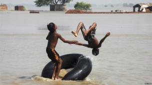 Village boys jump from a tyre tube into floodwaters at Danapur, on the outskirts of the eastern Indian city of Patna