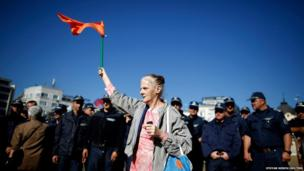A demonstrator waves a flag during a protest in front of the parliament building in Sofia