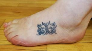 Tattoo on foot of happy and sad masks