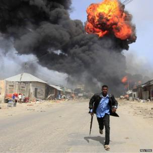 Somali policeman runs from the scene of an accidental explosion at a petrol storage facility within the former United States residential housing in capital Mogadishu - Tuesday 3 September 2013