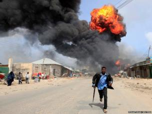 A Somali policeman runs from an accidental explosion at a petrol storage in Mogadishu