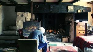 Artist Eleanor Brooks painting in front of her inglenook fire