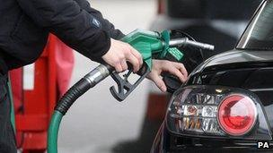 Person filling car at petrol pump