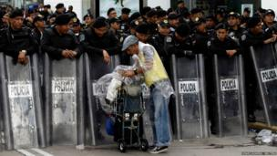 A street vendor sells soft drinks to Mexican riot police standing guard on the perimeter of the Benito Juarez international airport during a protest by teachers
