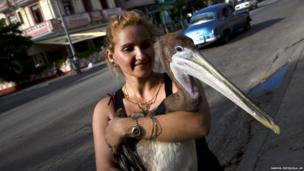 Magela Guerrero holds Pancho the Pelican as she poses for a photo in Havana, Cuba