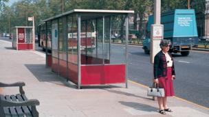 1959 photograph of a woman standing at a bus shelter
