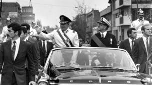 General Augusto Pinochet waves from the motorcade 11 September 1973 in Santiago