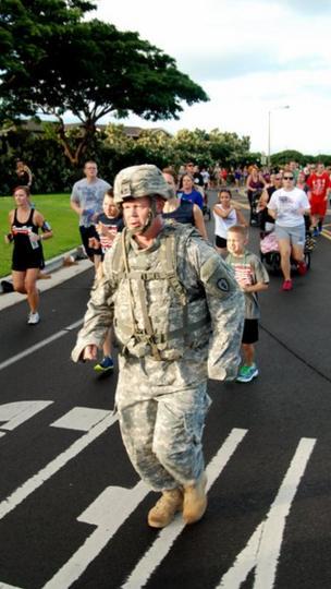 A soldier runs in full combat gear