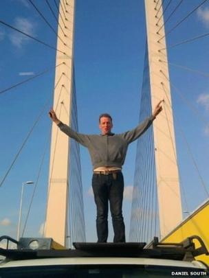 Stranded motorist poses on car while stranded on the Queen Elizabeth II bridge. Photo: Daniel South