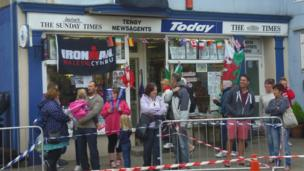 Crowds outside a newsagents in Tenby