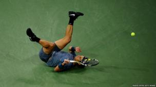 Rafael Nadal of Spain falls over during his men's singles final match against Novak Djokovic of Serbia