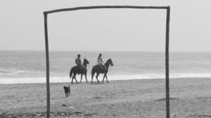 A couple ride horses on the beach