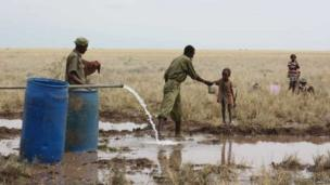 A Kenyan police reservist delivers clean water to a thirsty child at the Lotikipi Borehole