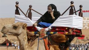 A young Moroccan girl uses her mobile phone on a camel at the Moussem festival in Tan Tan, southern Morocco on 7 September 2013