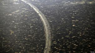An aerial view of Cairo's traffic and houses pictured through the window of an aeroplane on 11 September 2013