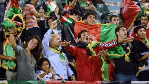 Afghan football fans cheer with their national flag during the SAFF Championship match between India and Afghanistan in Kathmandu on 11 September 2013.