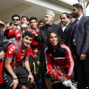 Afghan President Hamid Karzai poses with members of the national soccer team a day after they beat India 2-0 in the South Asian Football Federation Championship in Kabul, Afghanistan, on 12 September 2013.