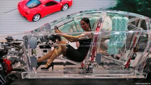 A woman sits in a car made of glass