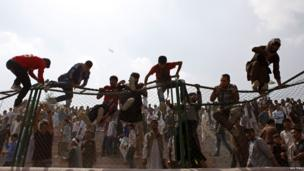 Afghan football fans climb over a fence to celebrate winning the South Asian Football Federation championship after their team defeated India during the final match, at Ghazi Stadium in Kabul on 12 September 2013.