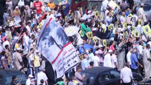 Protesters with placards and flags march. Photo: Ayman Ashwa