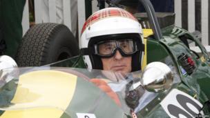 Racing driver Jackie Stewart in tartan helmet sits in classic race car. Photo: Dave Edwards