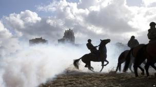 A horse bucks as it jumps over smoke from a grenade during a practice session for members of the Dutch cavalry in Scheveningen, Netherlands, Monday, Sept. 16, 2013.