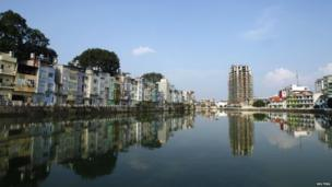 The construction site of a new office building is seen reflected on a lake in Hanoi.