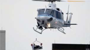 A helicopter rescues an apparent victim of a multiple shooting at the Washington Navy Yard, 16 Sept
