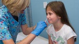 Girl being given flu vaccine nasally
