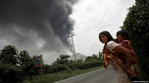 A woman and her daughter flee their home as Mount Sinabung erupts in Karo, North Sumatra, Indonesia