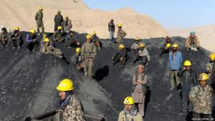 Afghan miners wait to remove the dead bodies of their colleagues following a mine collapse in Ruyi Du Ab