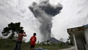 Indonesian youths watch as Mount Sinabung erupts in Karo, North Sumatra, Indonesia, Tuesday, 17 September, 2013.