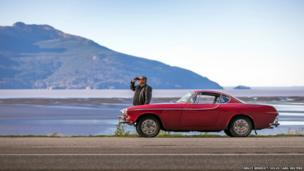 Irv Gordon is shown with his 1966 Volvo P1800 on Alaska Highway 1