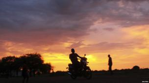 A man riding a motorbike at dusk in Abyei, which border Sudan and South Sudan - Saturday 14 September 2013