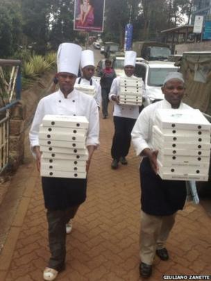 Chefs carrying boxes of pizza. Photo: Giuliano Zanette
