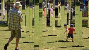 A man and a child navigate a maze of 81 mirrors