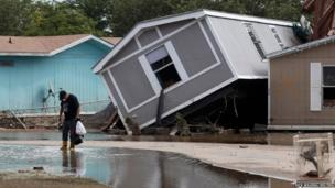 A resident of Eastwood Village retrieves belongings from his flooded home in Evans, Colorado