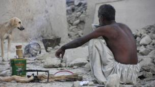 A survivor of an earthquake sits as he takes tea on rubble of a mud house after it collapsed following the quake in the town of Awaran