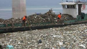 Workers collect floating rubbish near the Three Gorges reservoir