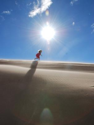 Girl running along sand dunes