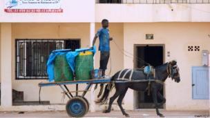 A man on horseback carries containers of water in a neighbourhood of Dakar