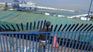 A young Moroccan passes through an opening in a fence surrounding the port of Tangiers, in northern Morocco, on Wednesday to board a boat illegally to Spain.