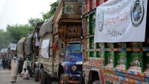 Pakistani drivers gather beside their trucks carrying earthquake relief supplies.