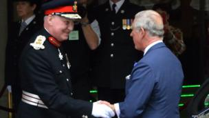 Prince Charles is greeted by police at the entrance to St David's Hall, Cardiff
