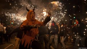 Man in devil's costume holds firework in the air during the 'Fire run' or Correfoc in Barcelona. Photo: Danny Fernandez